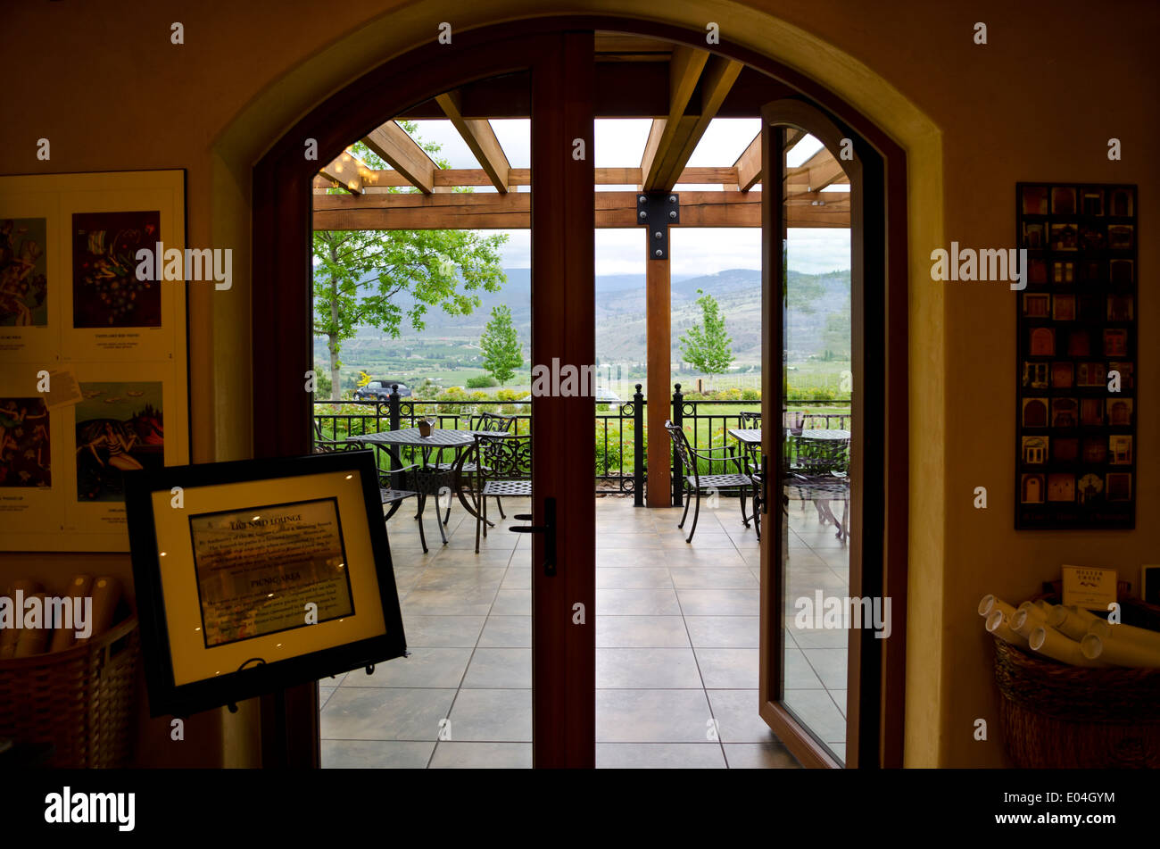Hester Creek winery tasting room looking through the doors out to the patio. Vineyards in the distance. Okanagan BC Canada & Hester Creek winery tasting room looking through the doors out to ...