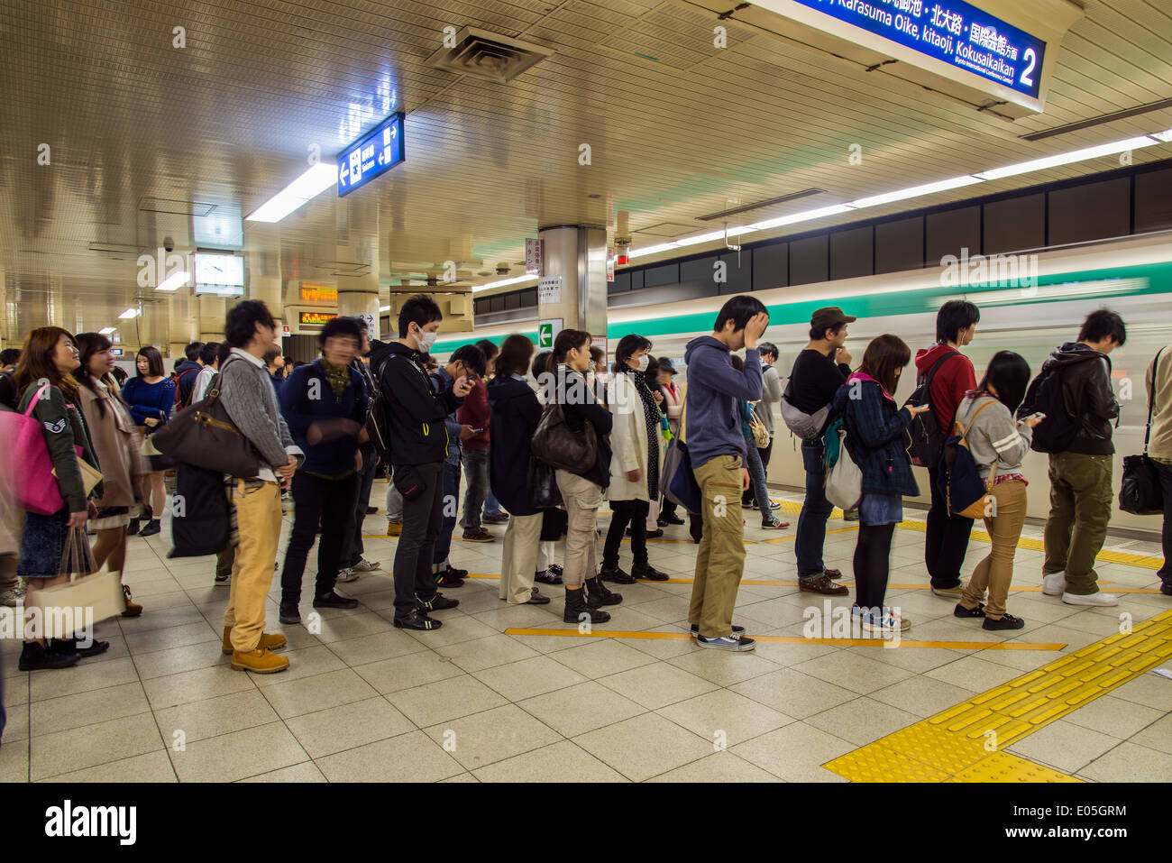 People on line waiting for the subway train, Kyoto, Japan ...
