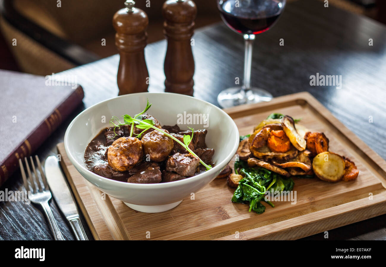 Rich Beef Stew With Dumplings Roasted Veggies On The Side Served With A Glass Of Red Wine