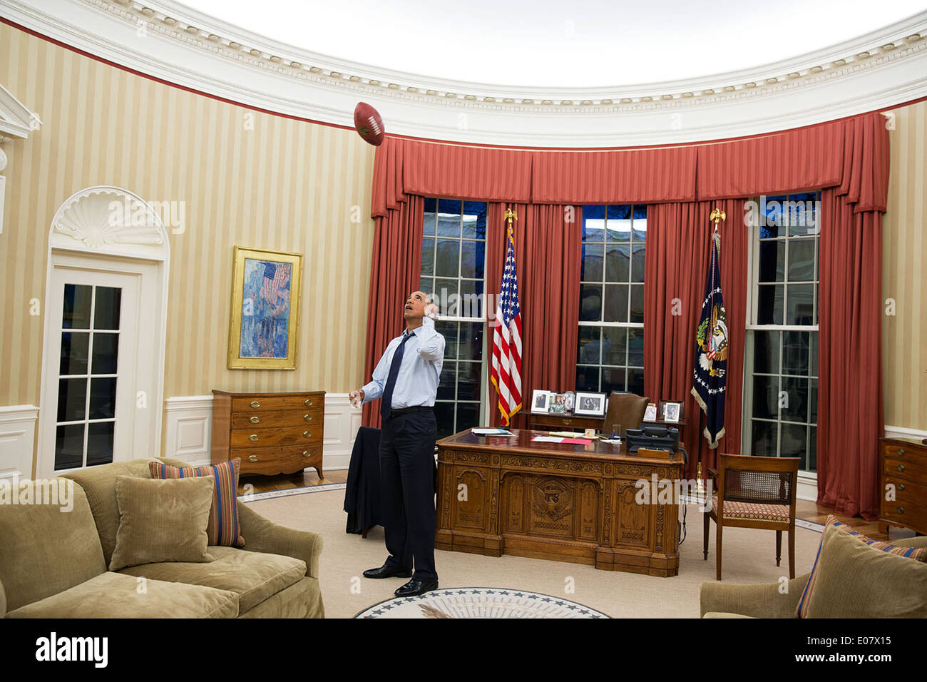 US President Barack Obama tosses a football in the Oval ...