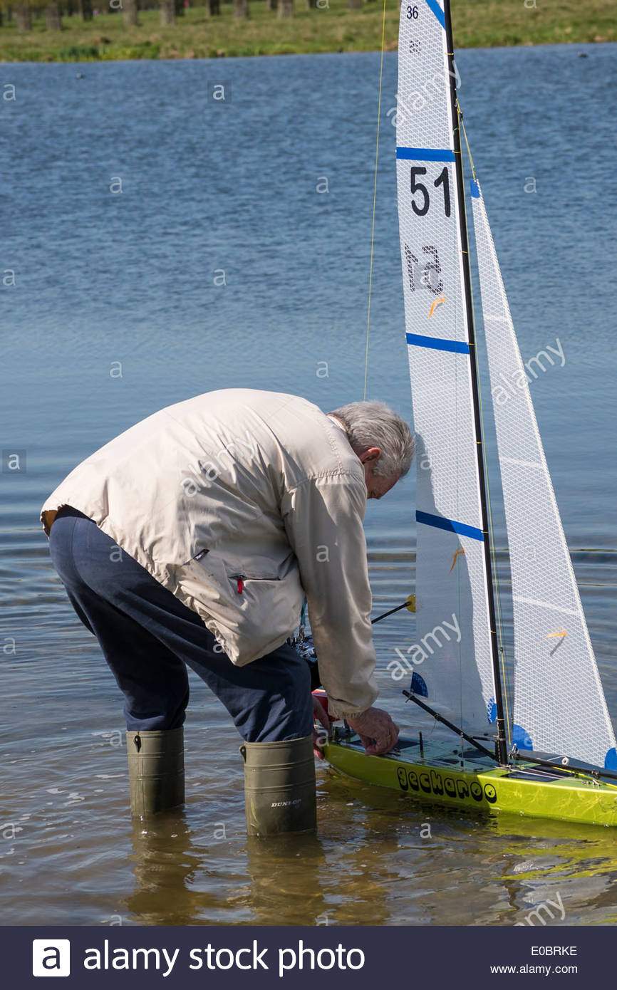 Elderly Man Sailing His Model Yacht On Rick Pond Home Park Kingston Surrey England UK