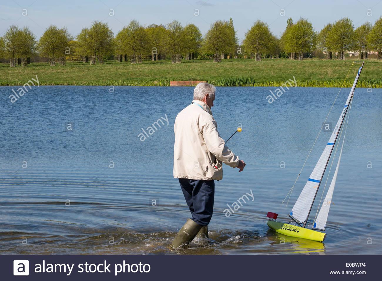 Elderly Man Sailing His Model Yacht On Rick Pond Home Park Kingston Surrey England UK