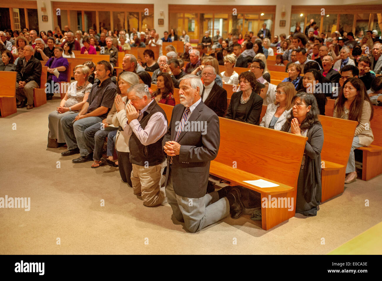 The Congregation Kneels In Prayer During Mass At St