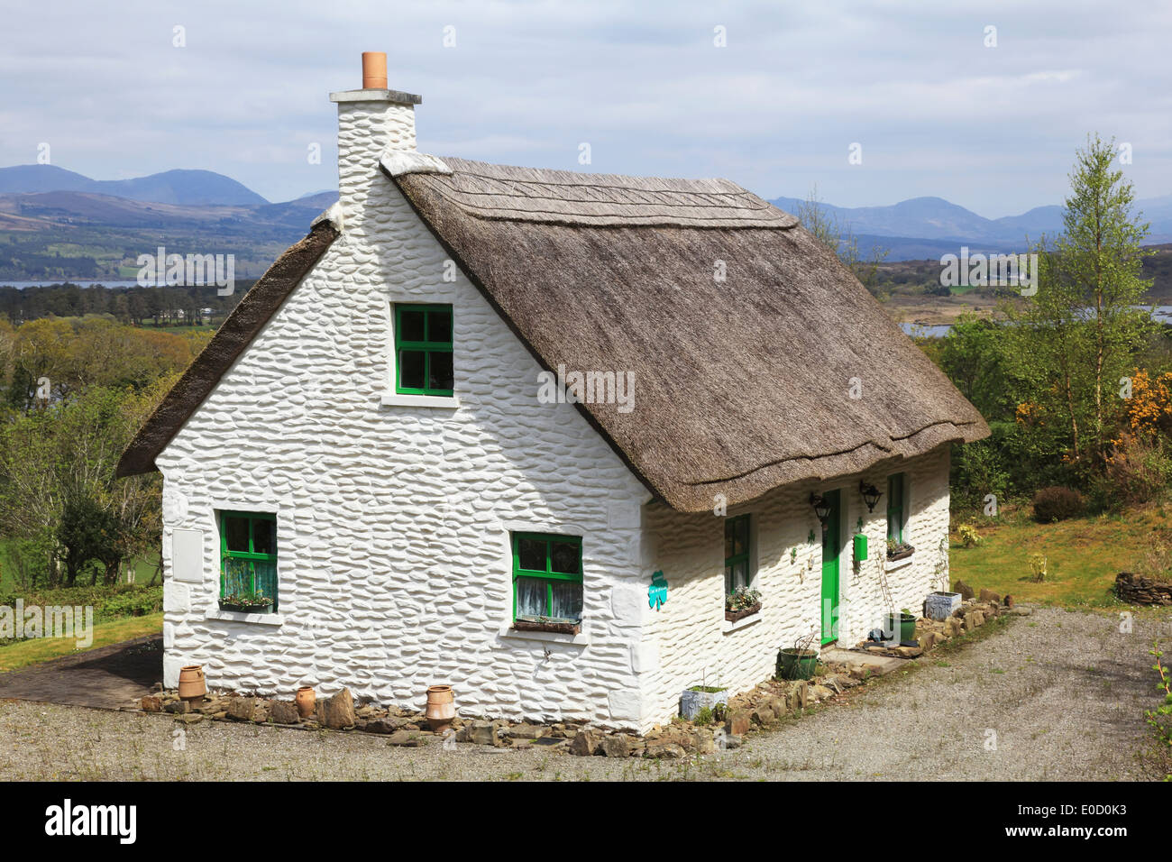 A white house with green door and trim and a thatched roof for White house green trim
