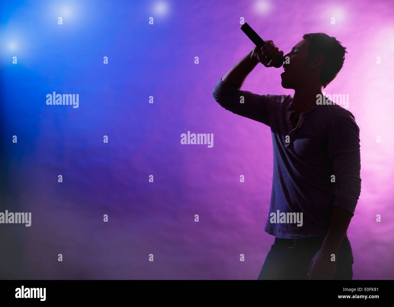 Silhouette of male singer on stage Stock Photo, Royalty ...