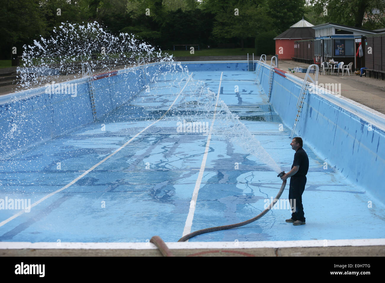 a man filling an outdoor swimming pool with a hose stock photo royalty free image 69220832 alamy