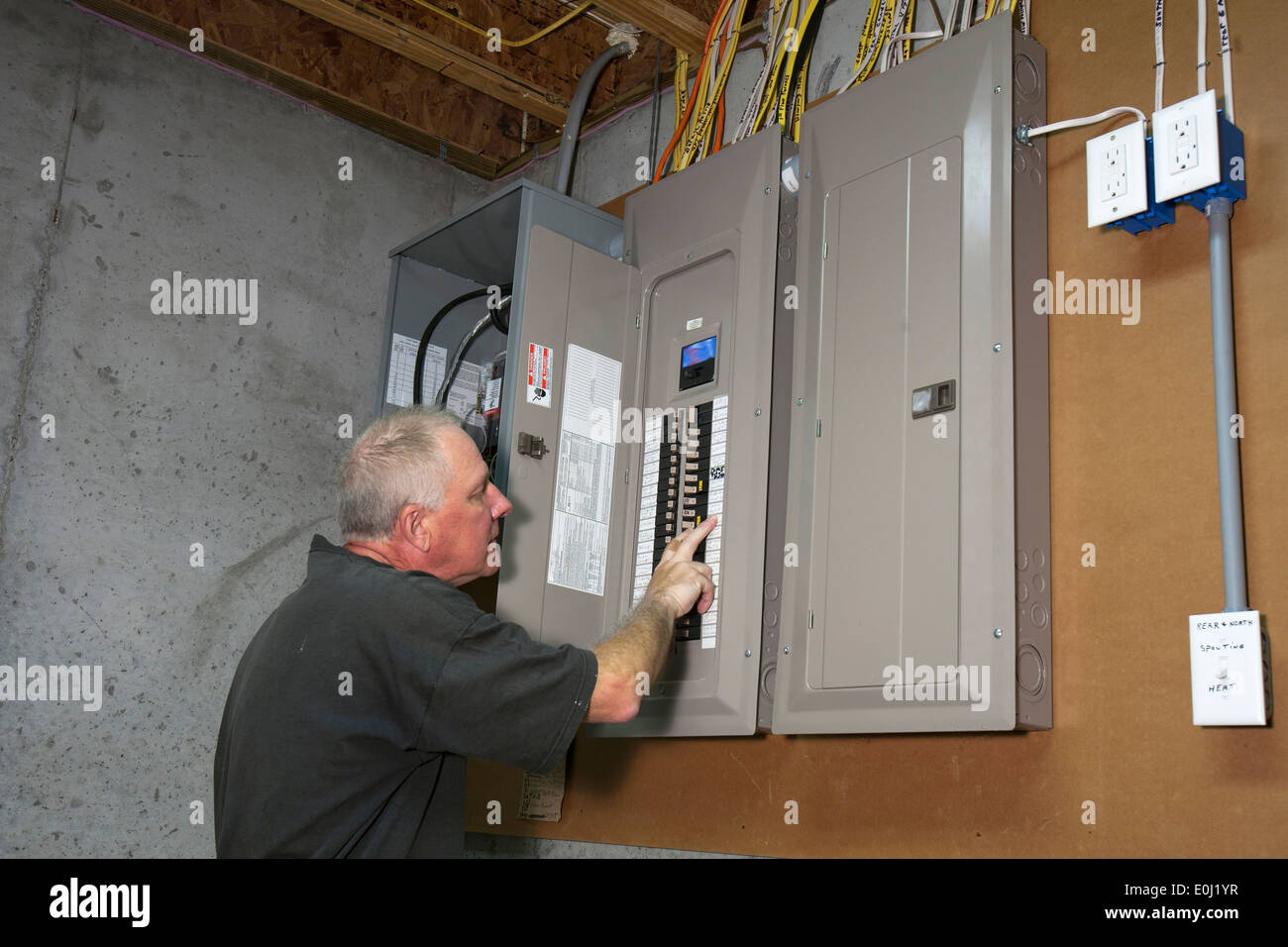man standing next to fuse box in a basement stock photo ... fuse box in basement fuse box basement ideas