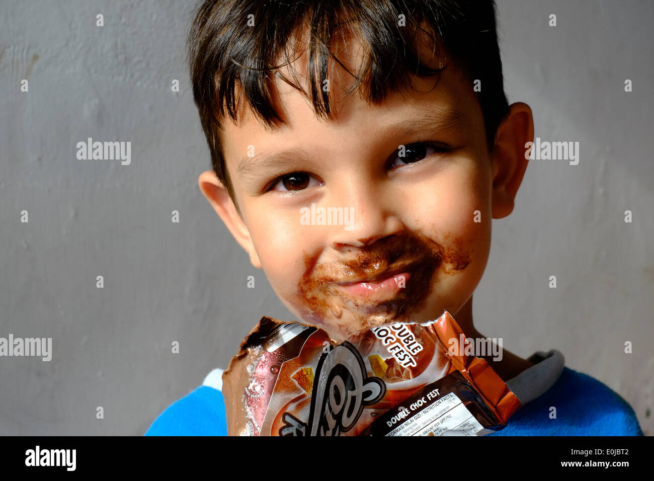 young boy eating a chocolate ice cream and getting most of it ...
