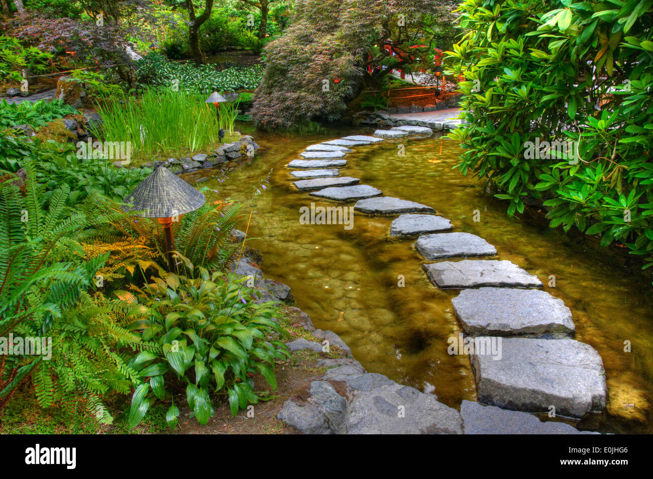 a stone path over a pond in butchart gardens victoria british