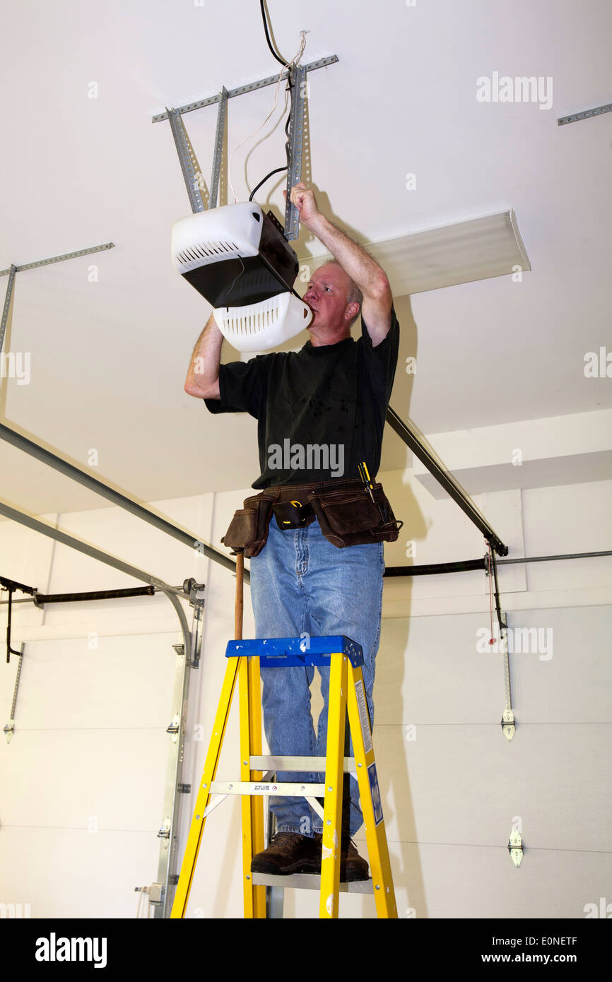 Man standing on a ladder fixing a mechanical garage door opener & Man standing on a ladder fixing a mechanical garage door opener ... Pezcame.Com