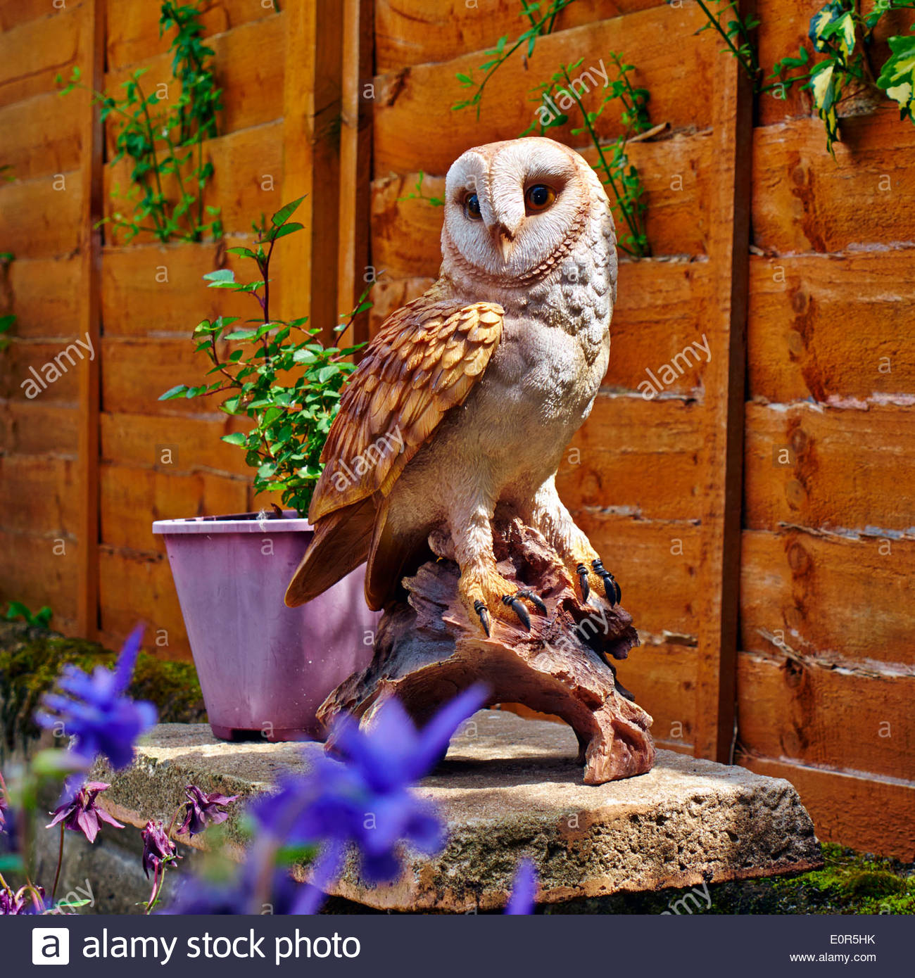 Ornamental owls for garden - Stock Photo Imitation Barn Owl Garden Ornament With A Miniature Rose In A Pink Container