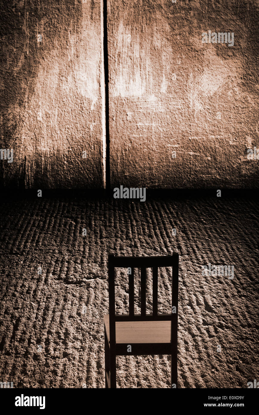 Empty chair in room - One Empty Chair In An Abandoned Room With Concrete Wall And Rough Grungy Floor Possibly Set Up For Interrogation Conceptual Image Of Loneliness