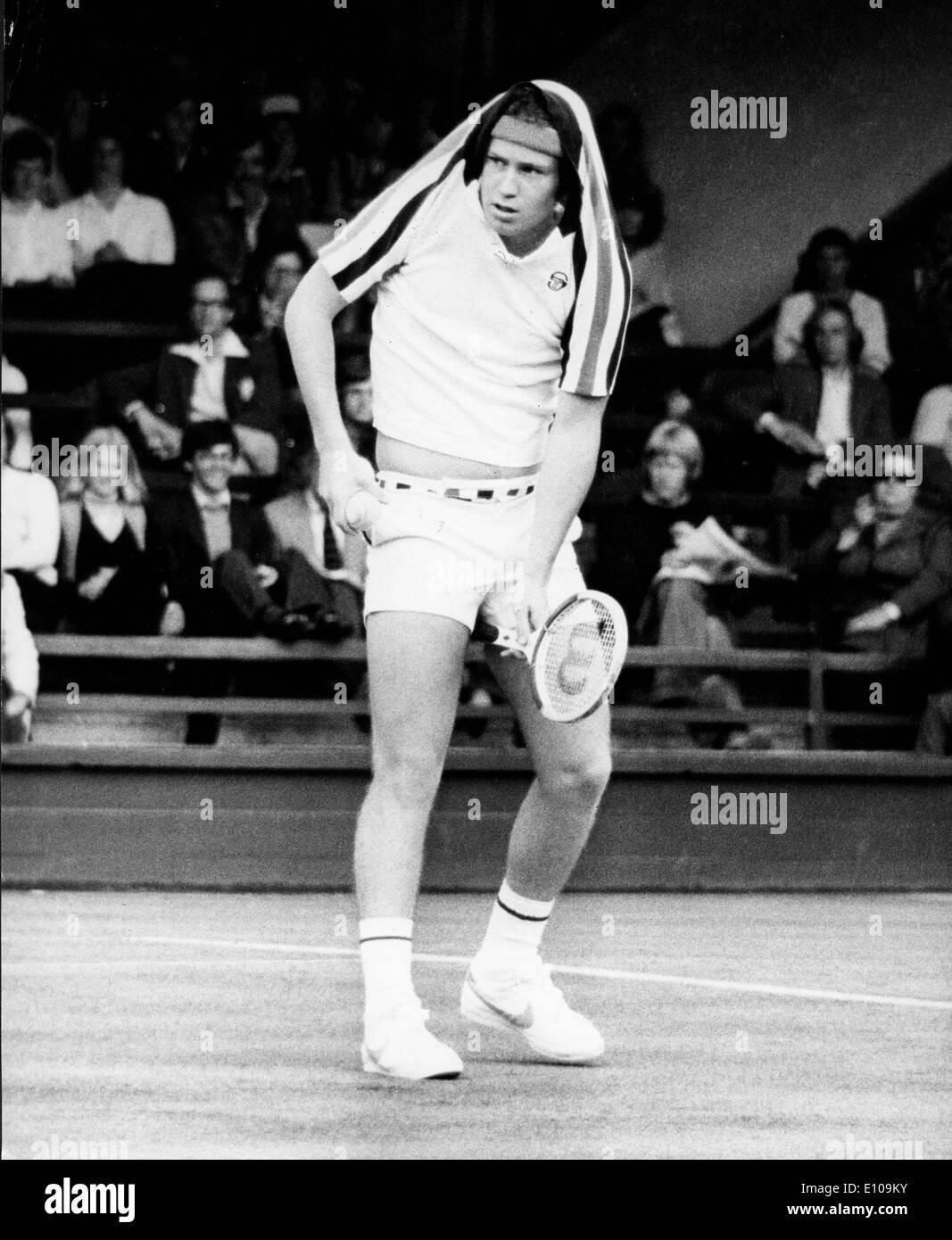 Tennis player John McEnroe covers head from rain Stock