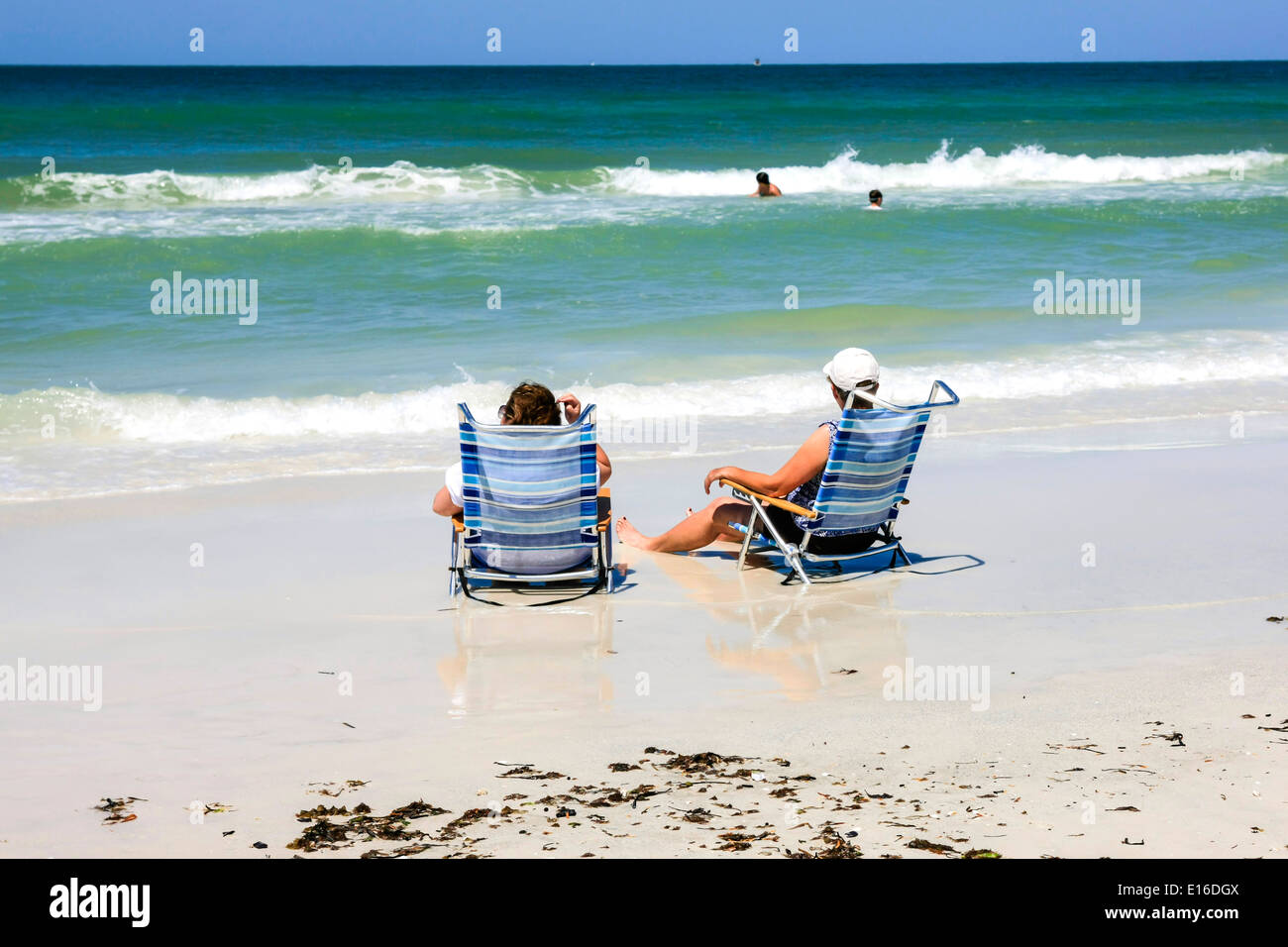 Two Women Enjoy Sitting In Beach Chairs On The Shoreline Of Siesta Key Beach  Florida