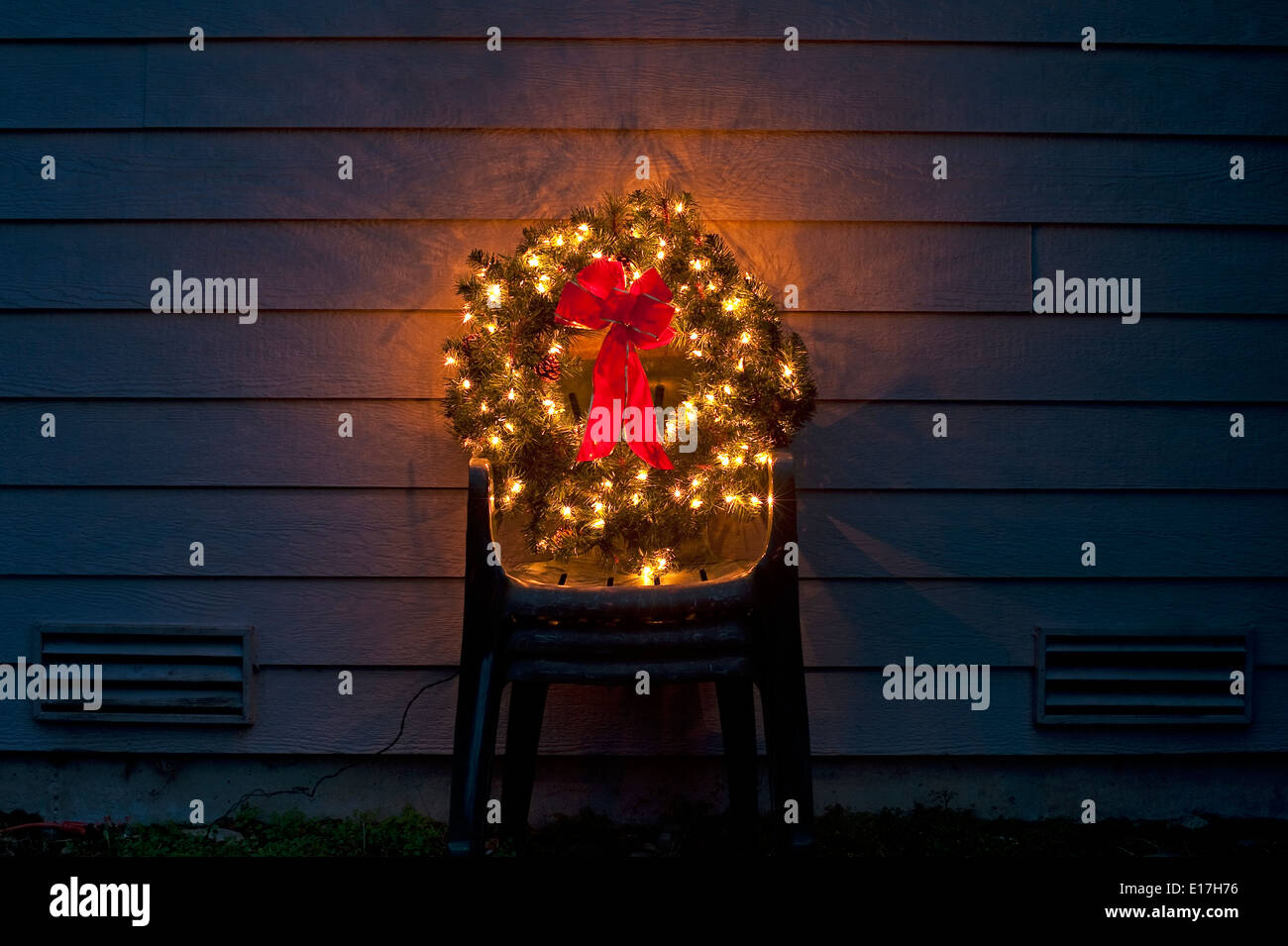 christmas wreath in backyard on stacked lawn chairs with christmas