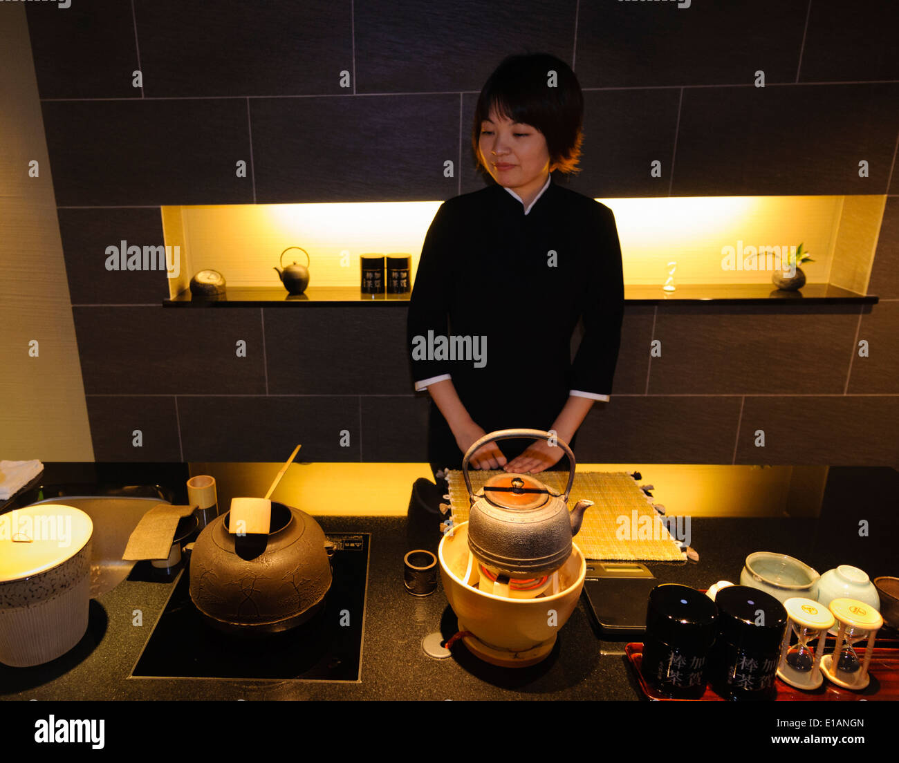 young female s assistant stands in a tea shop behind various stock photo young female s assistant stands in a tea shop behind various traditional apparatus used to prepare green tea matcha
