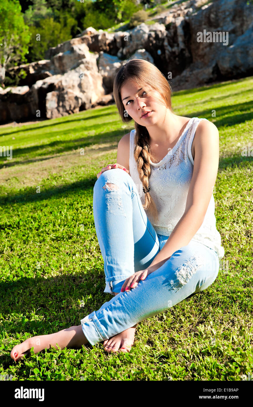 http://c8.alamy.com/comp/E1B9AP/barefoot-girl-in-ripped-jeans-sitting-on-the-grass-in-the-park-against-E1B9AP.jpg