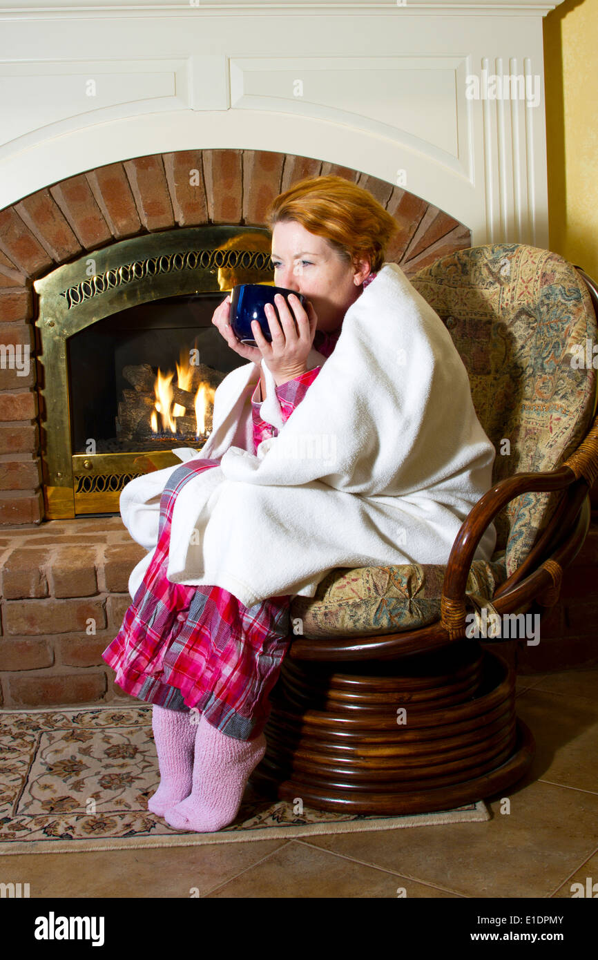 Mature Woman Dressed In Flannel Pajamas Sitting In A Chair In ...