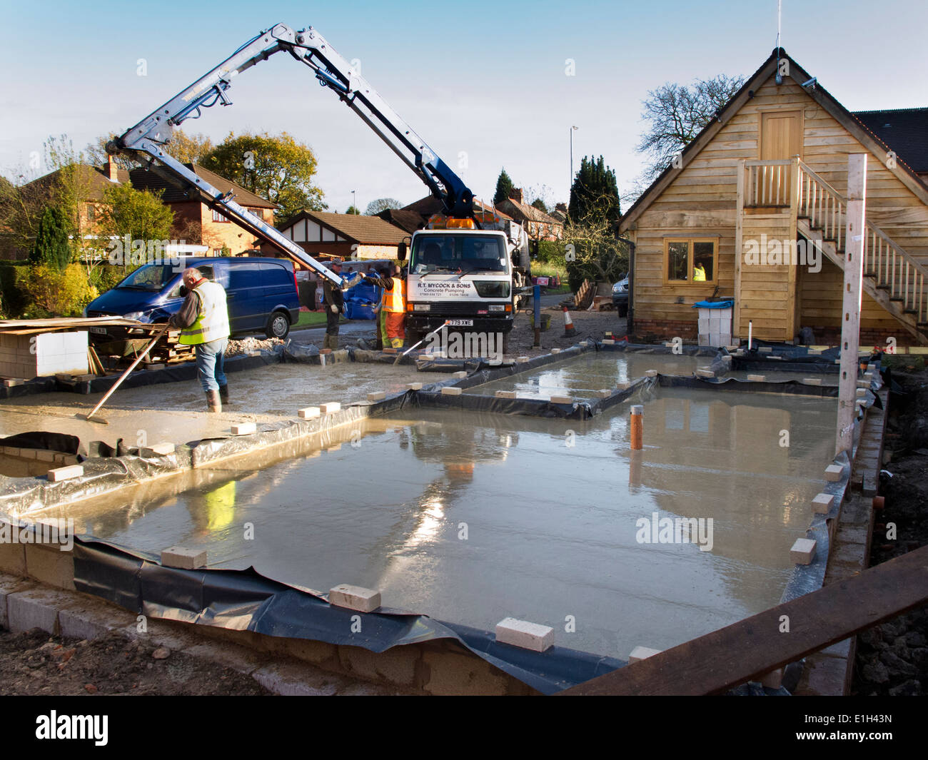 Self building house man tamping freshly poured concrete for Slab built homes