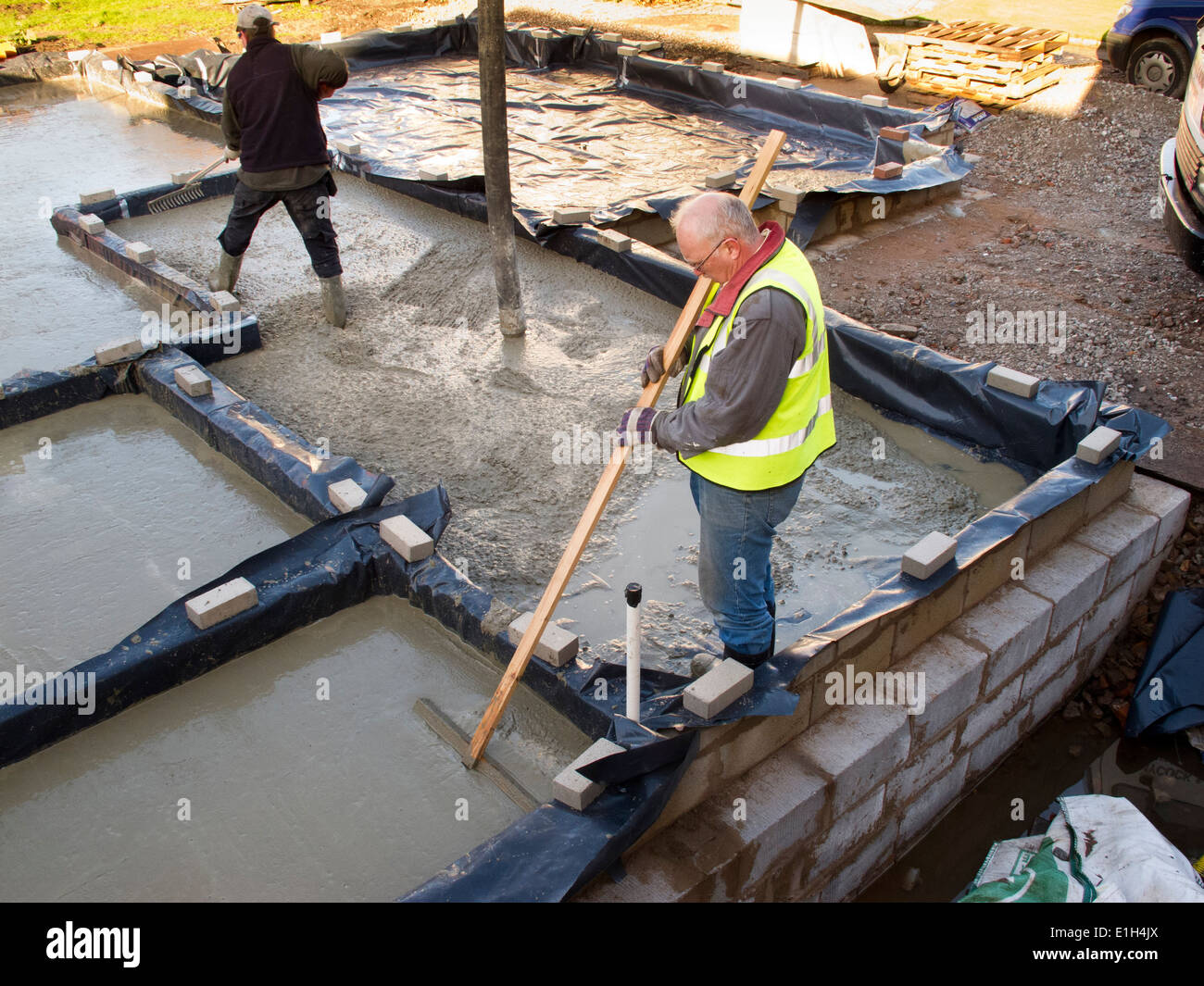 Self building house pouring floor slab man levelling for Building a house on a slab