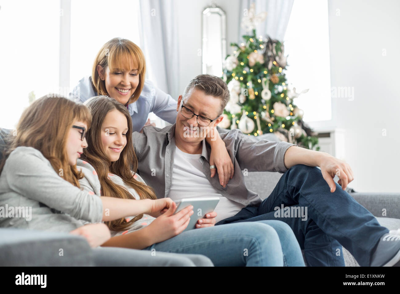 Perfect Family Using Tablet PC On Sofa With Christmas Tree In Background