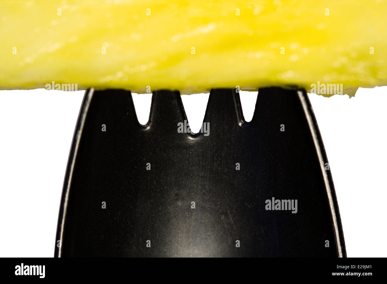 Plastic Spork Cut Out Yellow Pineapple Chunk Atop A Black Plastic Spork On
