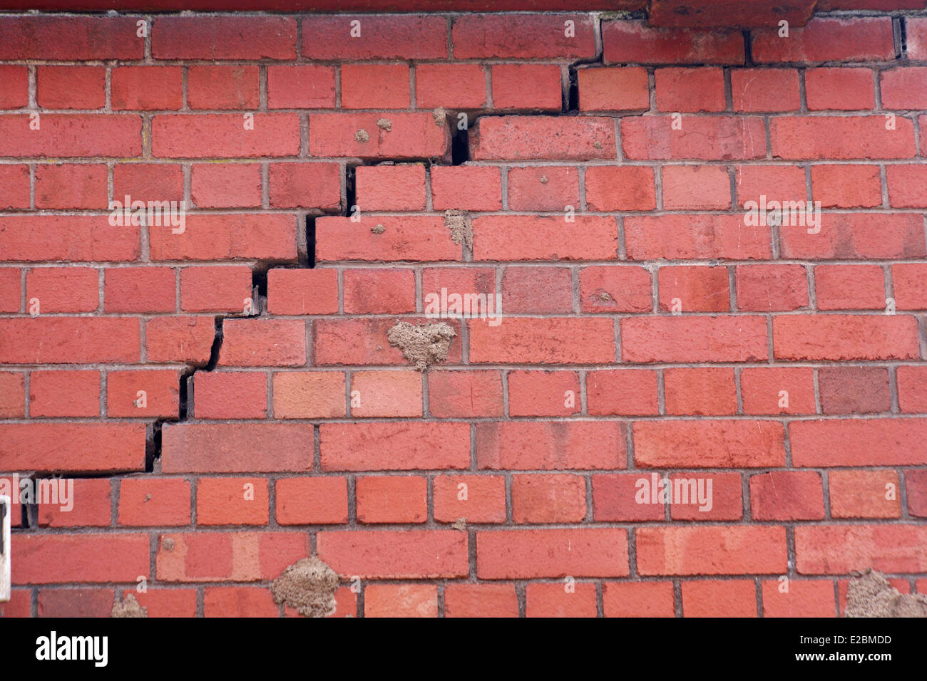 split wall brick wall with crack opening up stock photo