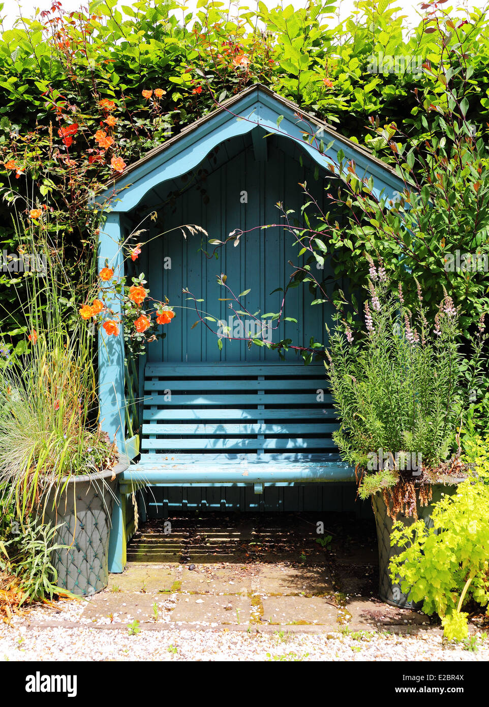 Covered Seat In An English Garden With A Hedge And