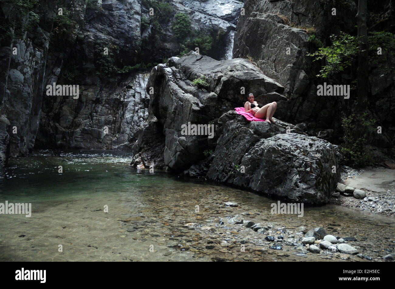A woman lying rock near a waterfall on the Fonias River ...