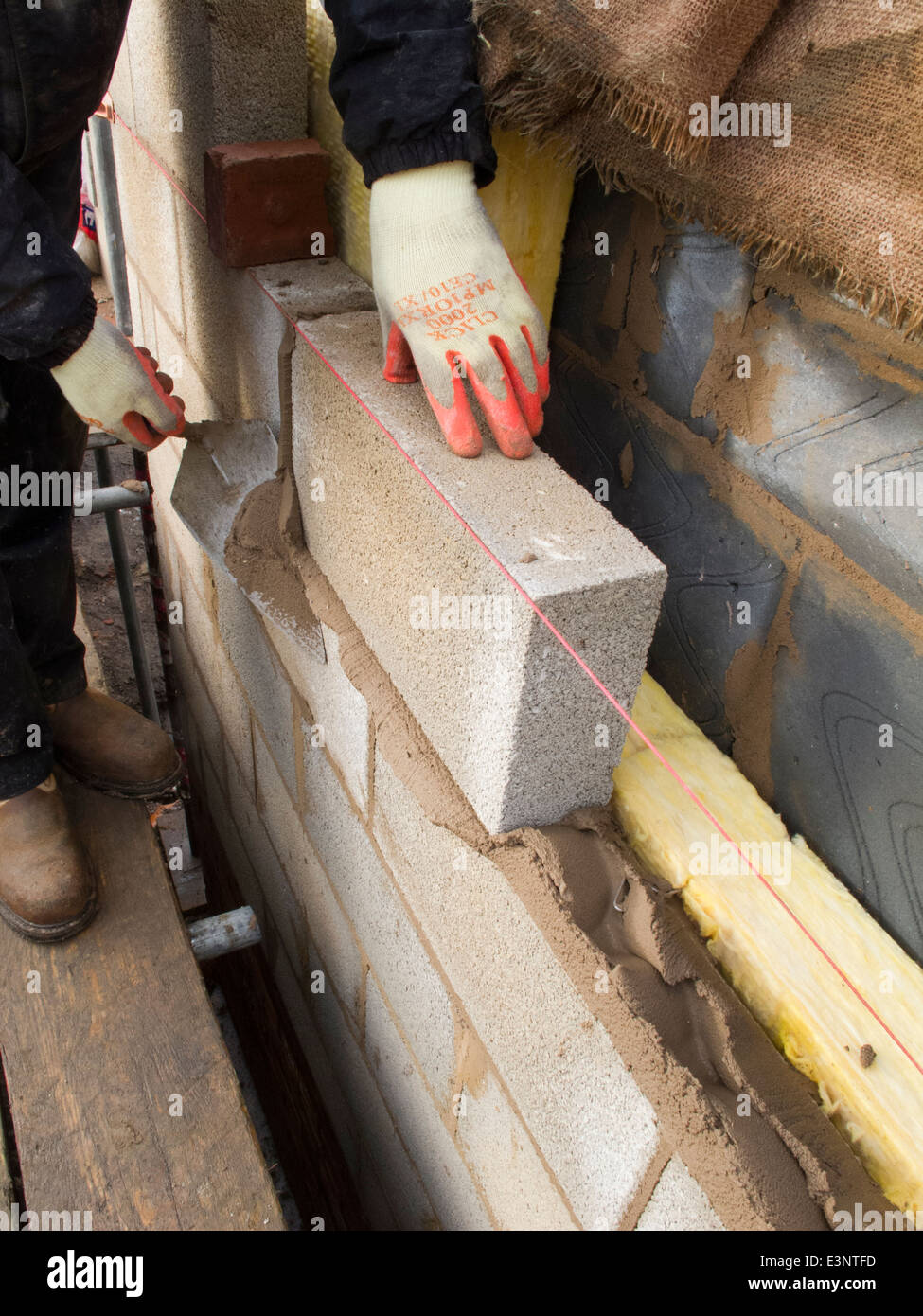Self building house bricklayer laying concrete block wall for Insulated cement blocks