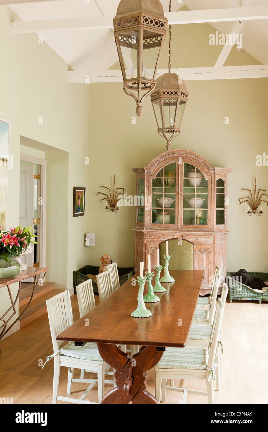 Old French Farmhouse Table In Dining Room With Swedish Style Chairs And Antique Cupboard