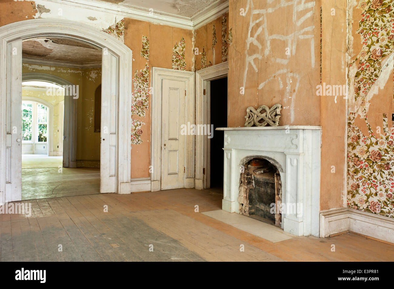 old bricked up fireplace in empty room with peeling wallpaper and
