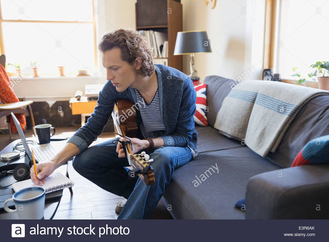 Musician with guitar writing music in living room Stock Photo