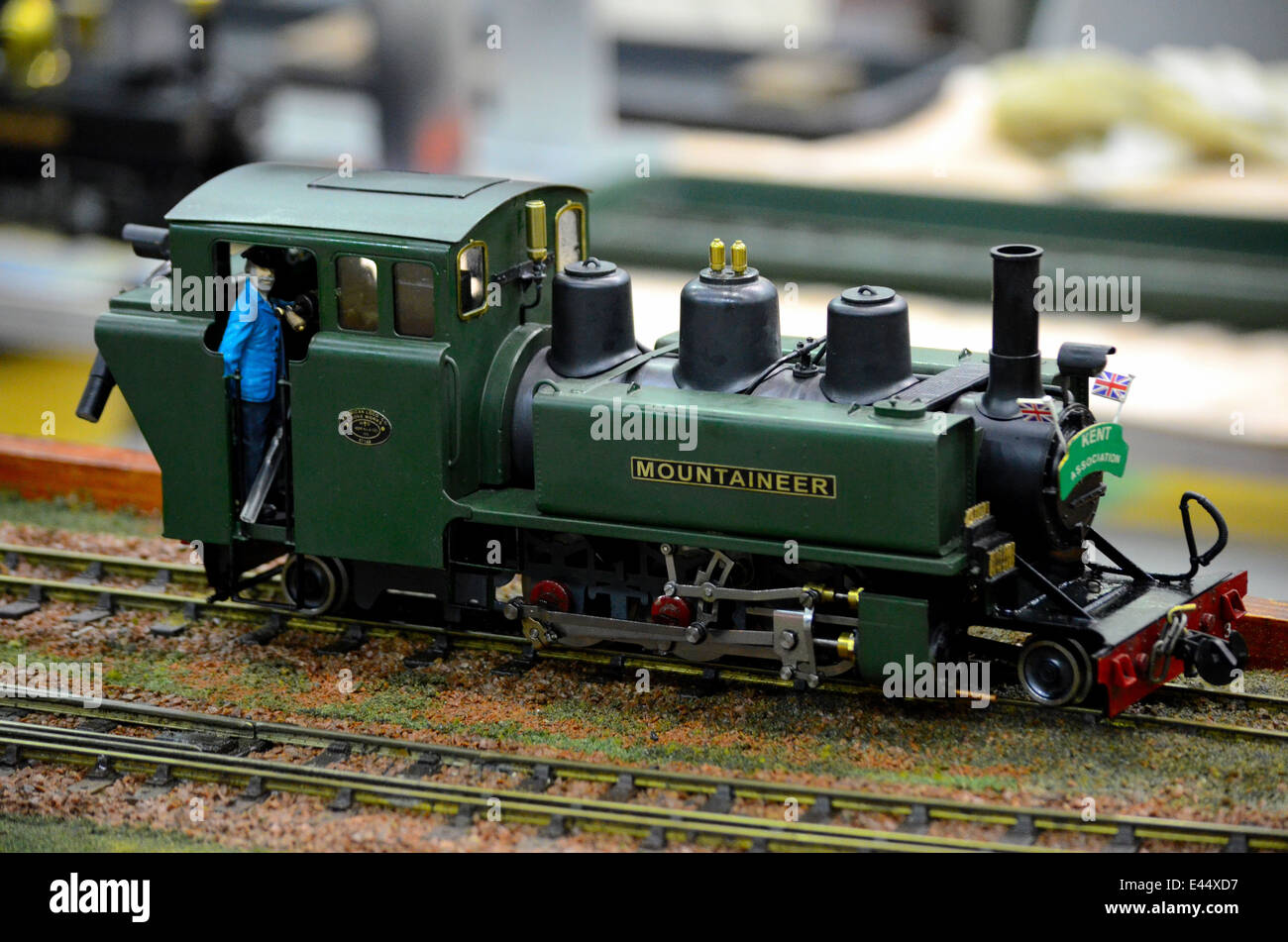 model train green steam railway engine with driver in cab stock