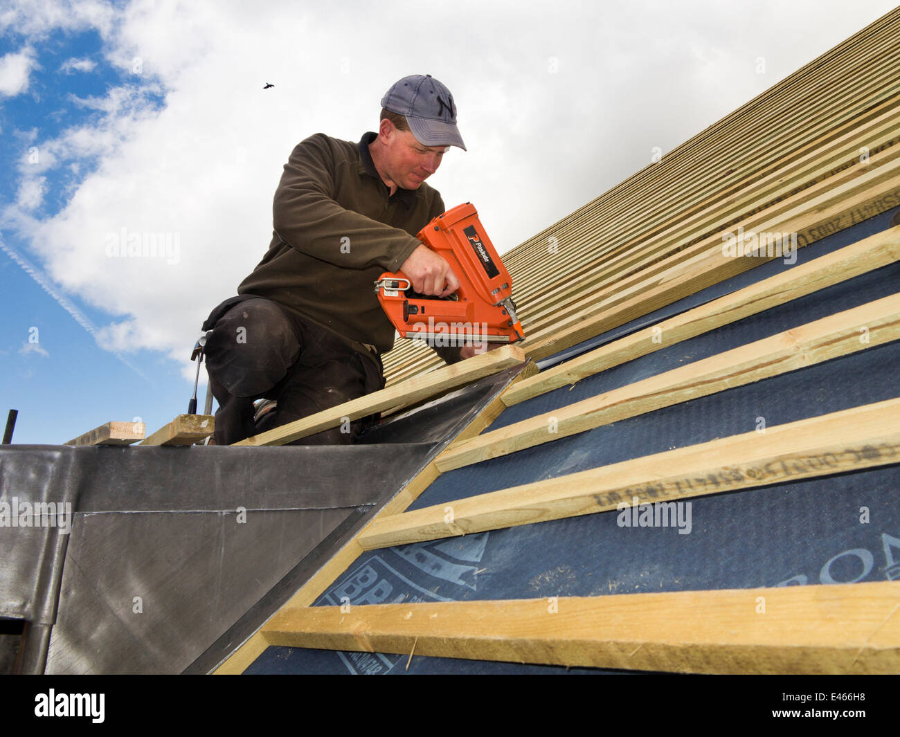 Self building house constructing roof man fixing roofing for Construct a house online