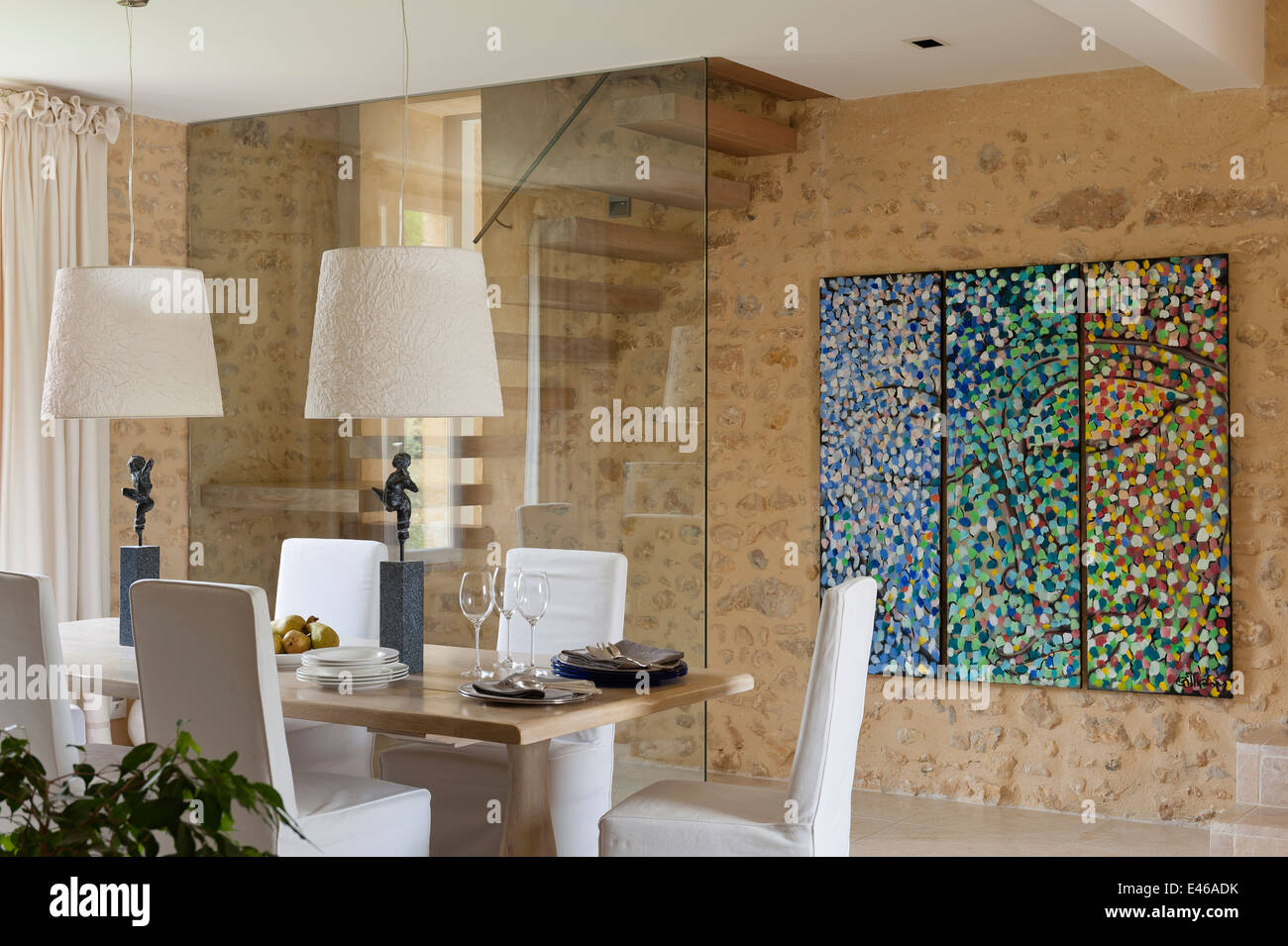 Dining Room With Abstract Painting On The Wall And Table Two Lampshades