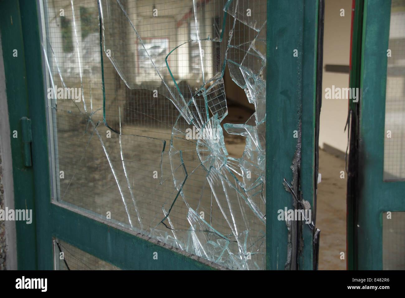 broken glass door with green metal frame stock photo