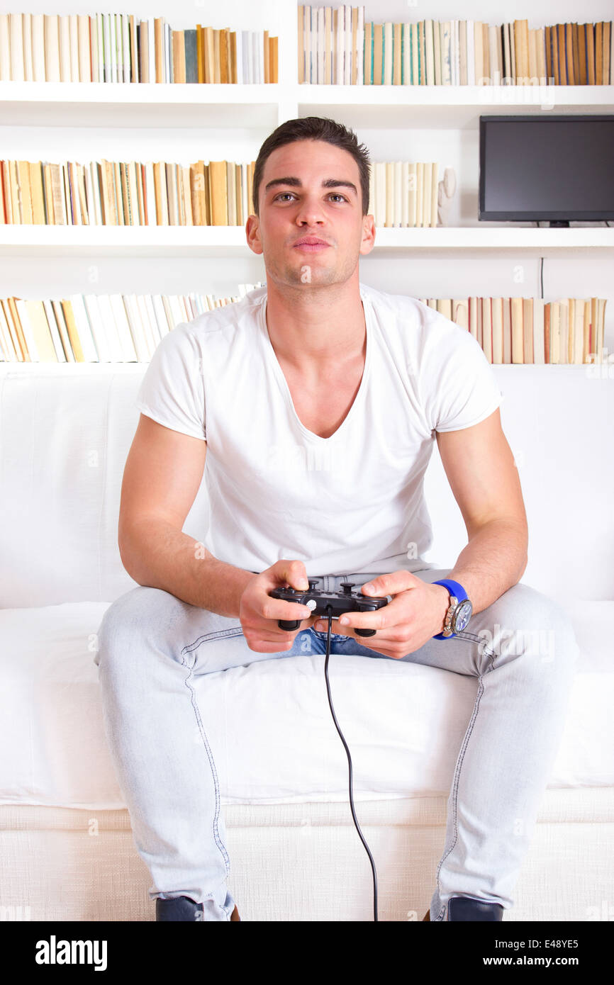 handsome guy playing video game at home sitting on couch Stock ...