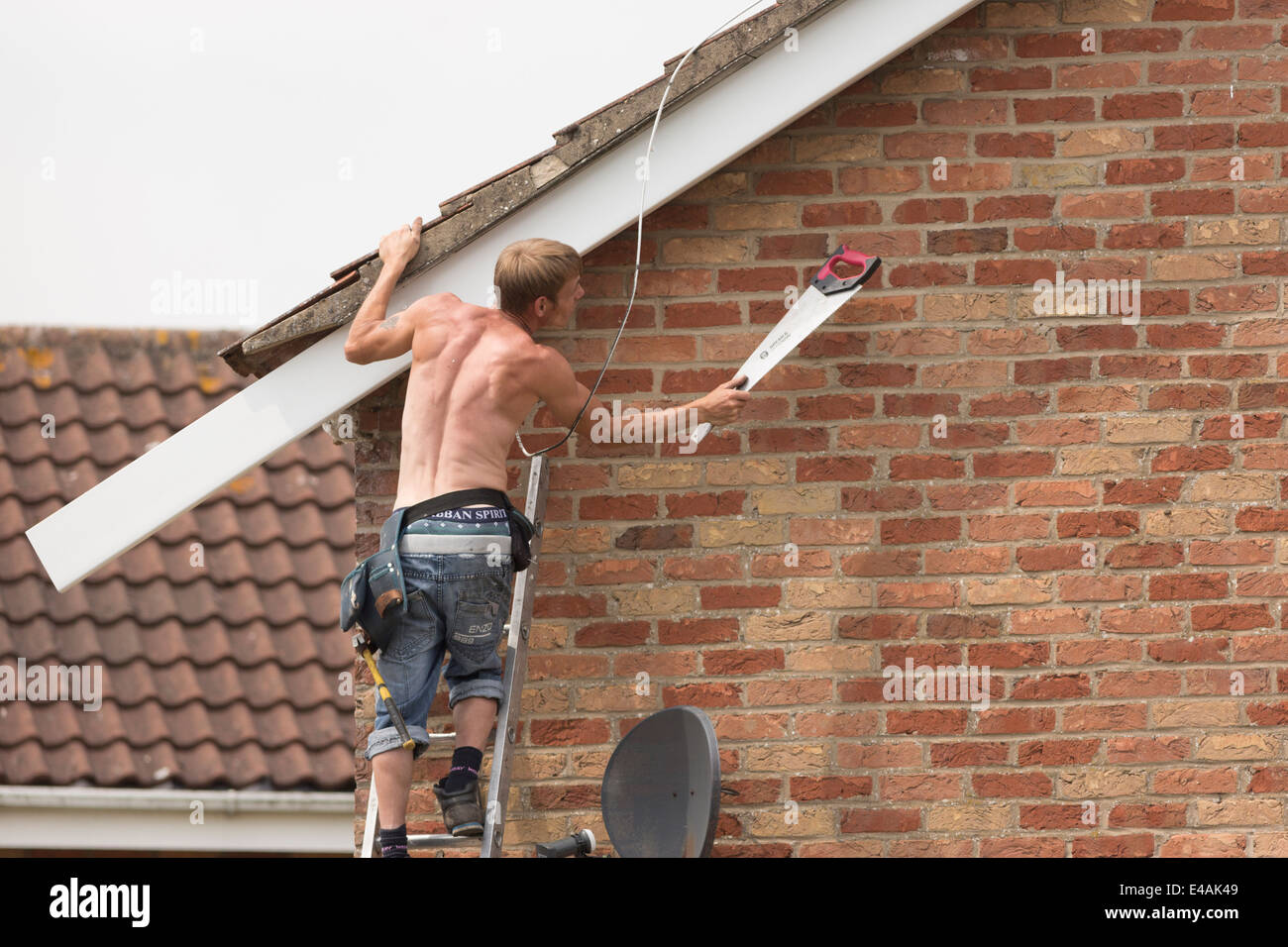 Replace fascia boards in sections - Workman Replacing Fascia Boards On A House Roof Stock Photo