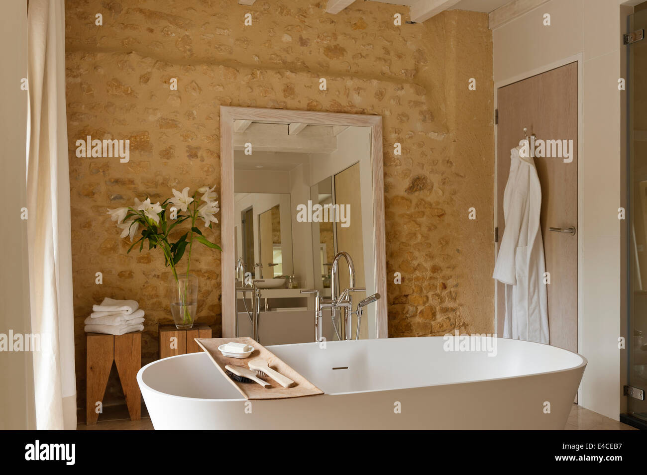 A Deep VAS 910 bath from Agape in bathroom with rough stone walls ...