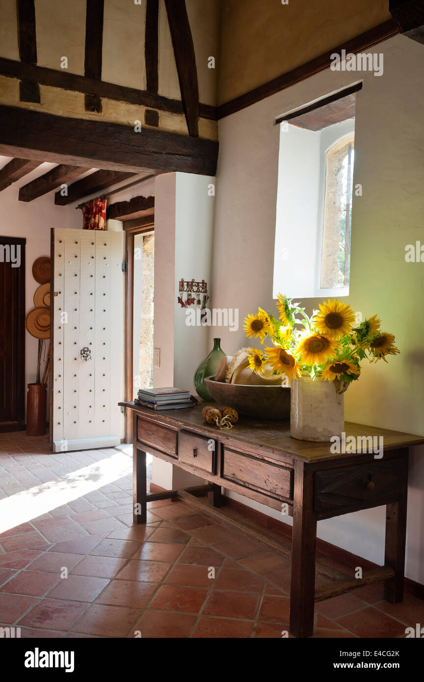 Jug Of Sunflowers On Old Wooden Console Table In Entrance Hall With Studded  Door And Terracotta Tiled Floor