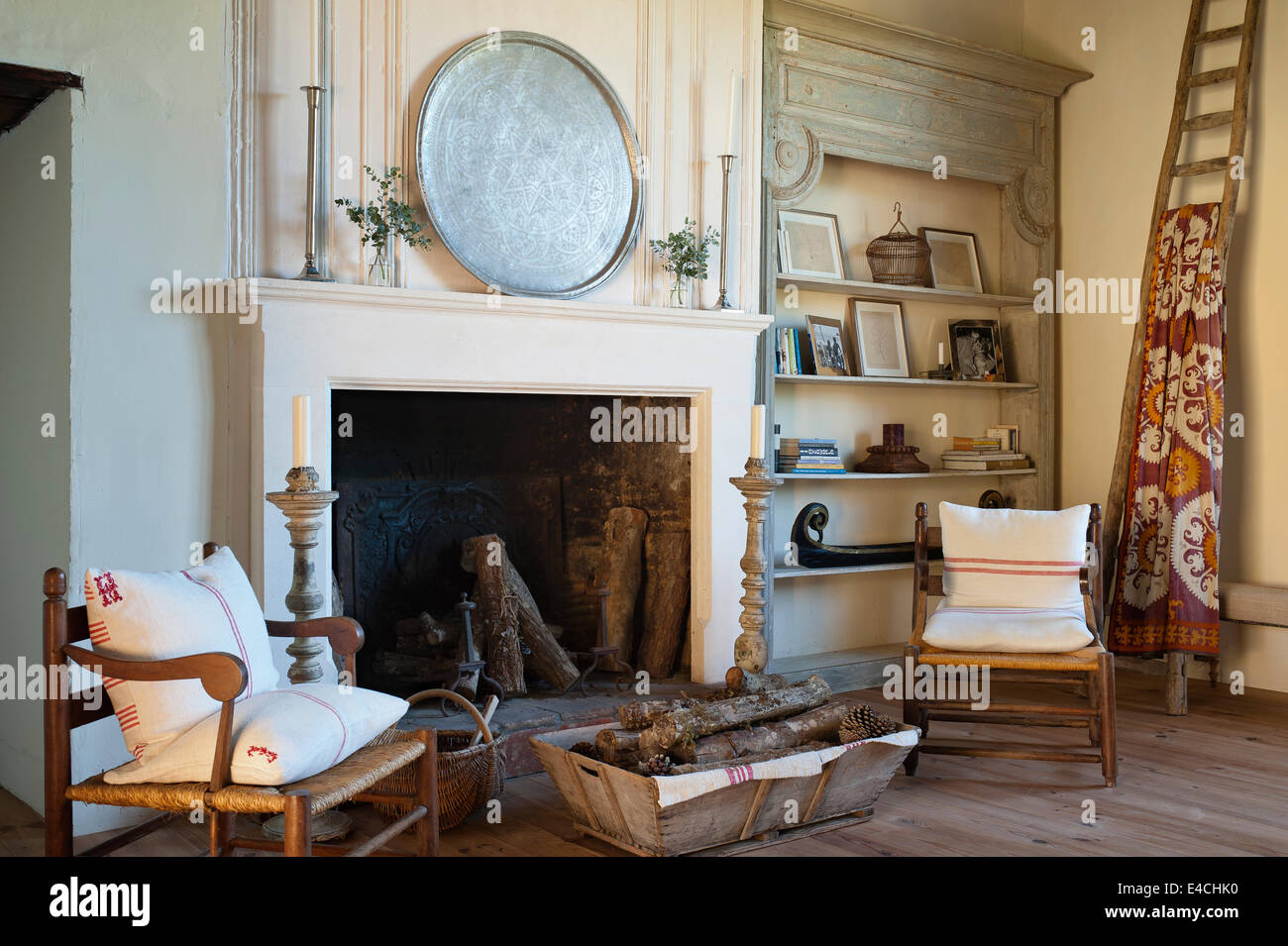 wooden armchairs and log basket by large open fireplace in