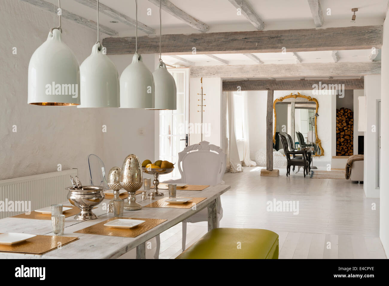 large white pendant lights hanging above an antique cherry wood dining table in open plan living space with wooden ceiling beams - Pendant Lights In Dining Room