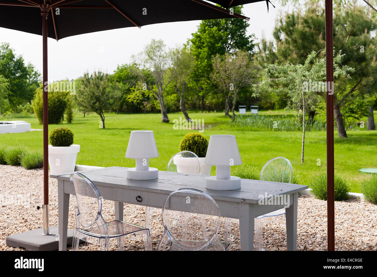 Garden Lights On Wooden Table With Philippe Starck Ghost Chairs Under Parasol In Garden Stock
