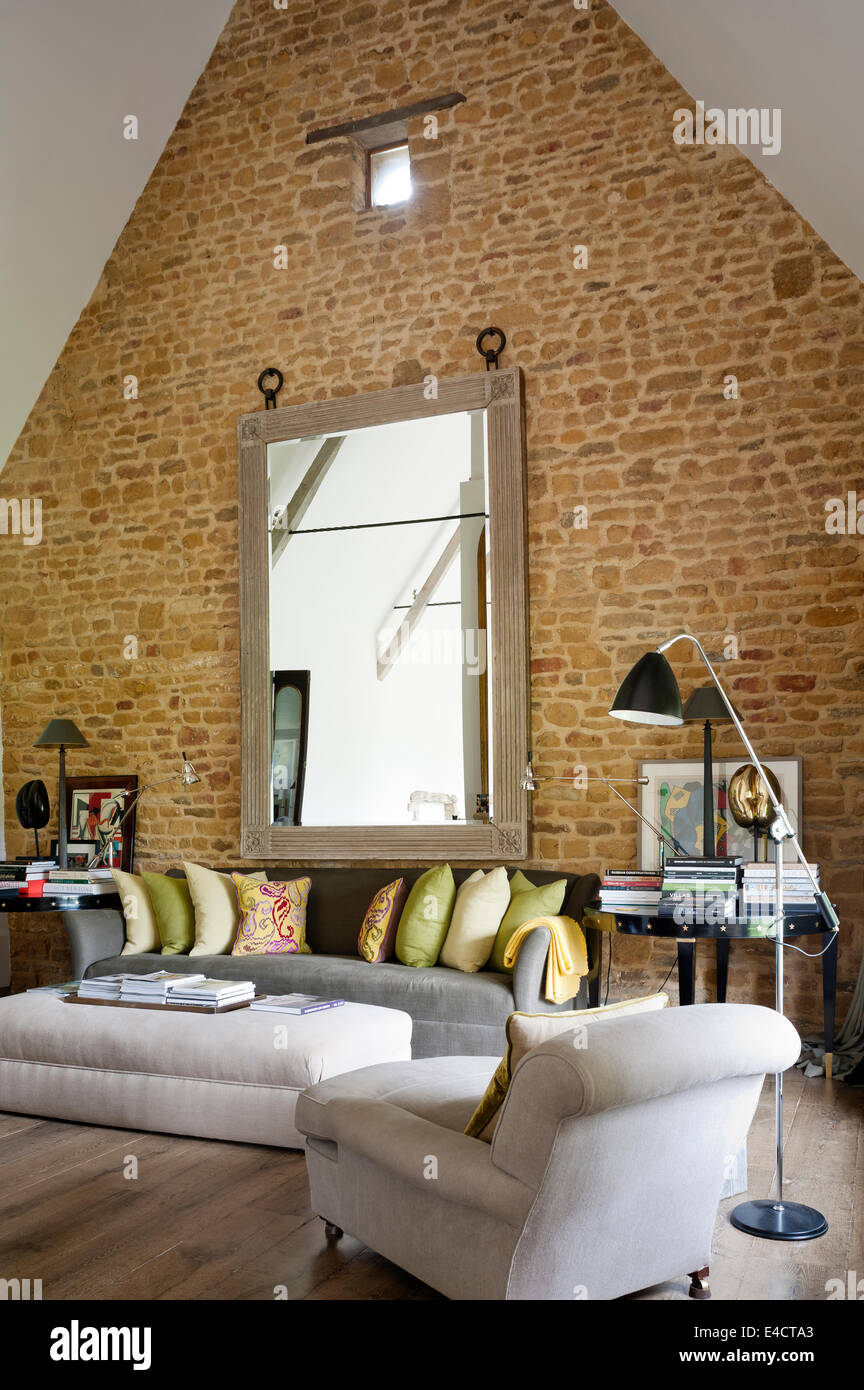 Exposed Brick Wall In Living Room With Pitched Ceiling And Large Mirror