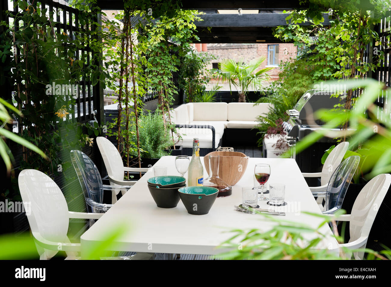 Philippe Starck Louis Ghost Chairs Around White Table On Roof Terrace With  Trellis