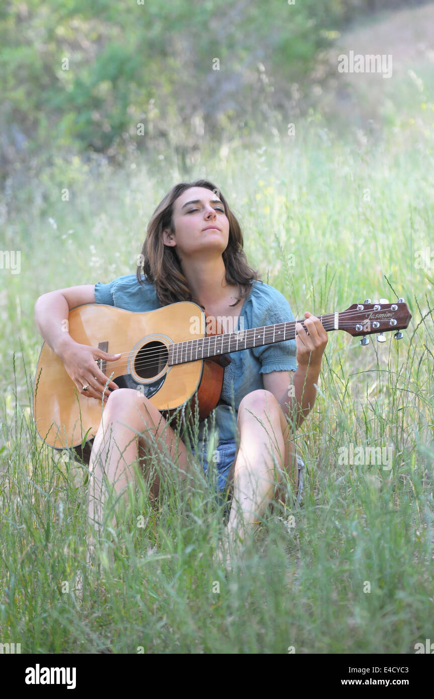 Brunette Girl Playing Guitar In A Field Outside Smiling