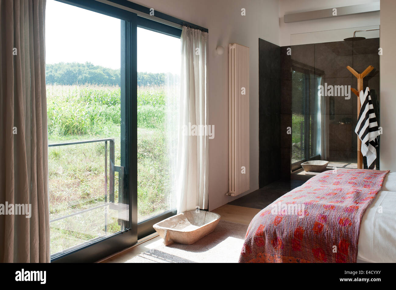 French windows for bedroom - Patterned Quilt On Bed In Bedroom With Ensuite Shower And French Windows With Rural Views