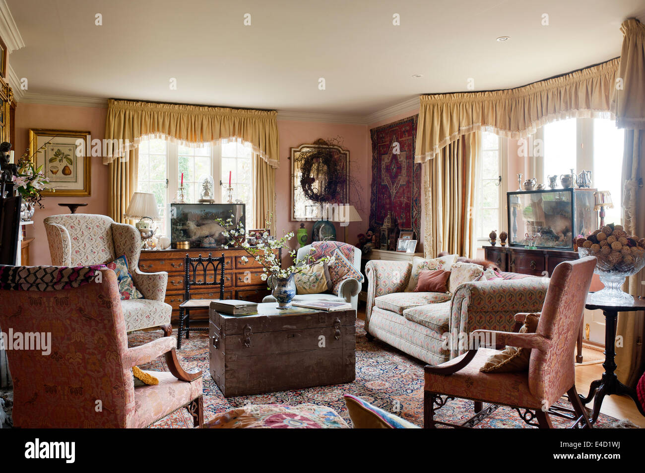 Living room floral upholstered sofa and wing back chairs in drawing room with old chests assorted textiles