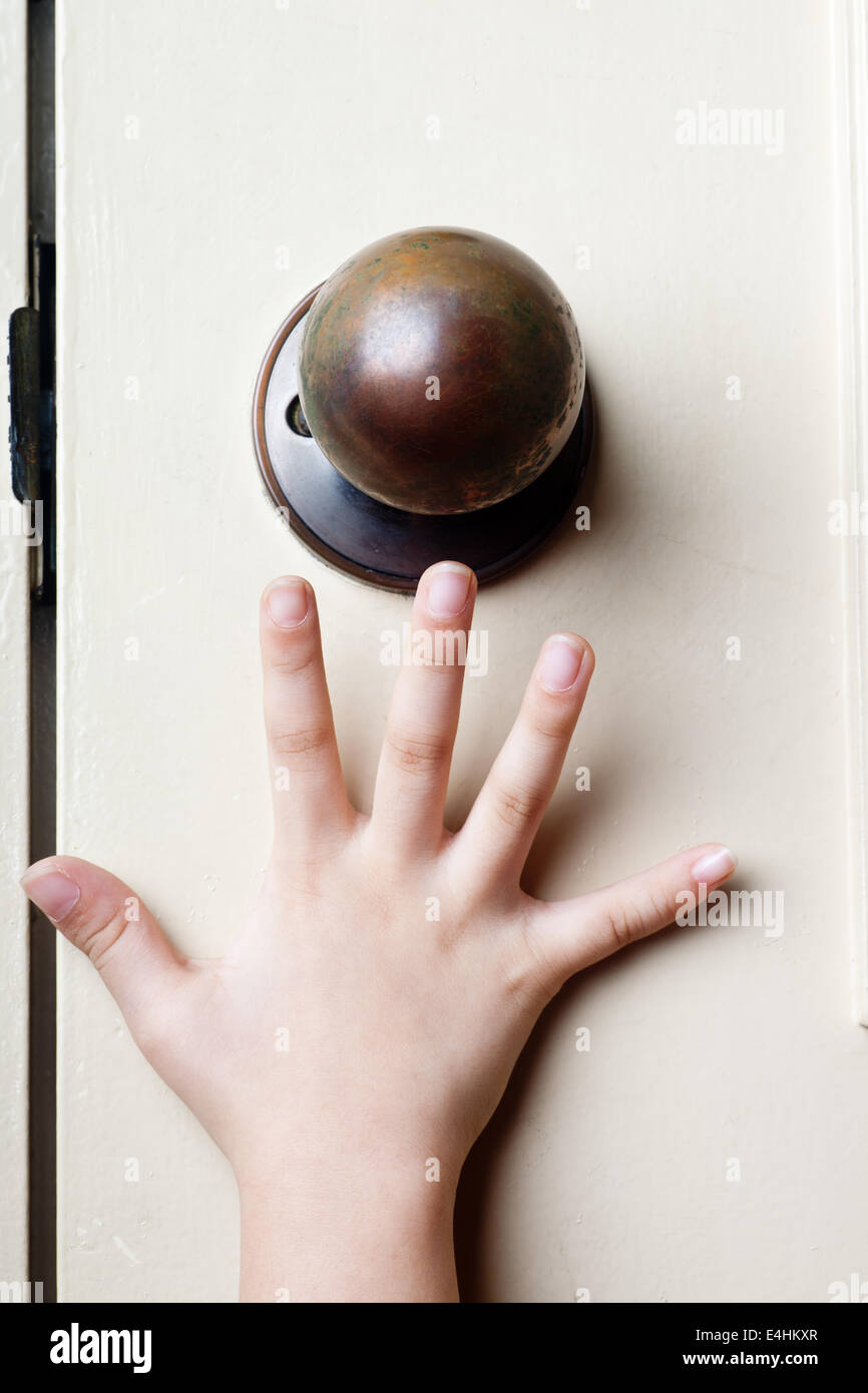 Kids hand reaching up for the door knob to open it Stock Photo